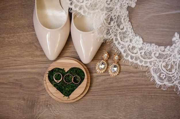 Acessórios de noiva. sapatos de noiva, véu, brincos, frasco de perfume, cinto de ligas e alianças em caixa de anel em forma de coração com musgo