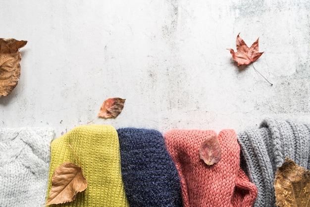 Acessórios de outono e folhas na superfície surrada