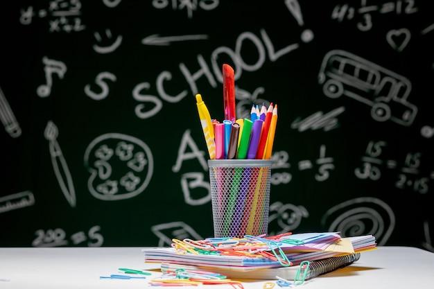 Acessórios de papelaria escolar. livros, globo, lápis e vários materiais de escritório sobre a mesa em uma lousa verde.
