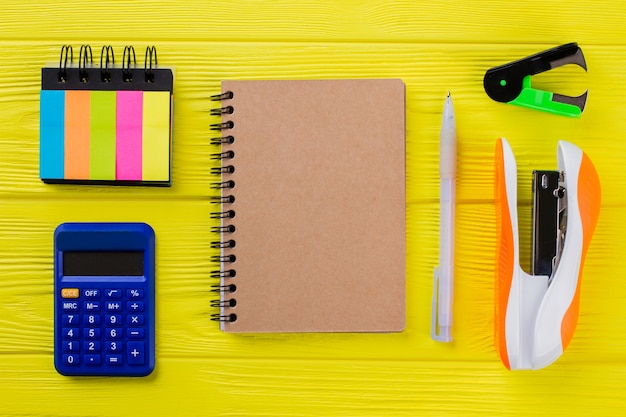 Acessórios de papelaria plana leigos na mesa amarela. bloco de notas com calculadora e grampeadores.