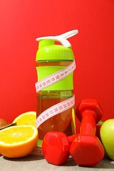 Acessórios de perda de peso na mesa cinza contra o fundo vermelho