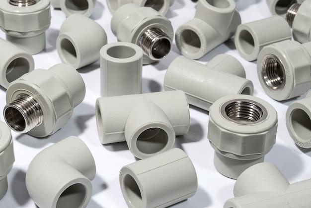 Acessórios de plástico para tubulações de água de poliprileno na superfície branca