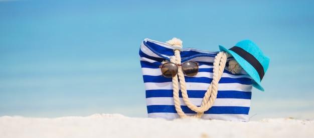 Acessórios de praia - bolsa azul, chapéu de palha, óculos de sol na praia branca