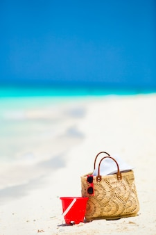 Acessórios de praia - bolsa de palha, chapéu branco e óculos de sol vermelhos na praia