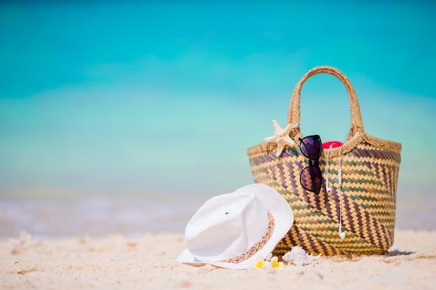 Acessórios de praia - bolsa de palha, chapéu branco, estrela do mar e óculos de sol pretos na praia. conceito de praia verão