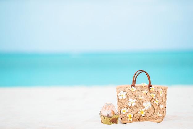 Acessórios de praia - bolsa de palha, chapéu e óculos de sol na praia