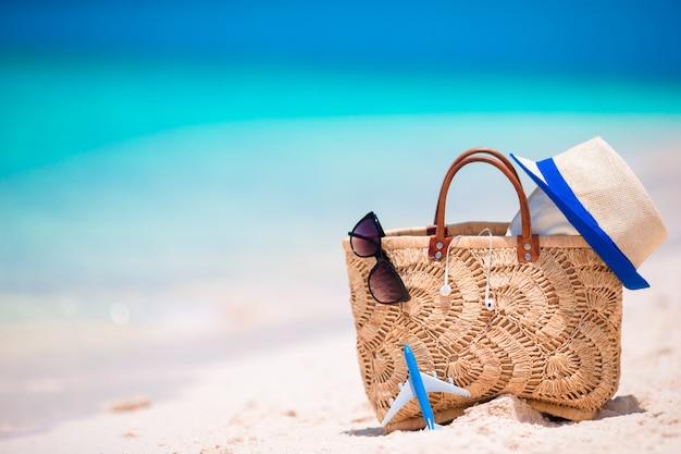 Acessórios de praia - bolsa de palha, fones de ouvido, avião de brinquedo e óculos de sol na praia