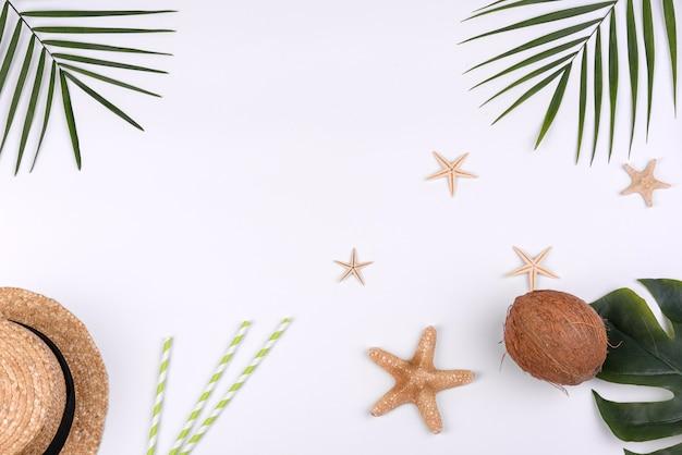 Acessórios de praia: chapéu com conchas e estrelas do mar em fundo branco. fundo de verão