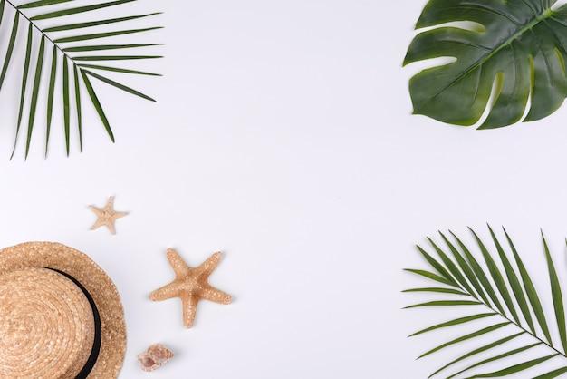 Acessórios de praia: chapéu de palha com conchas e estrelas do mar em um fundo branco. fundo de verão Foto Premium