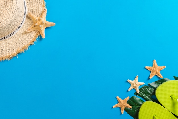 Acessórios de praia com chapéu de palha e conchas do mar azul