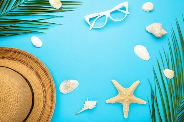 Acessórios de praia com folhas de palmeira sobre fundo azul