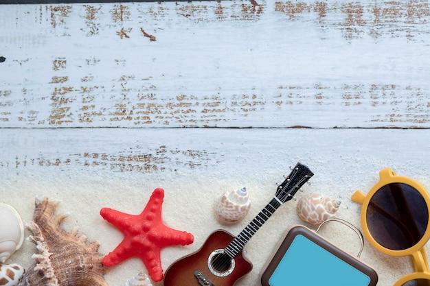 Acessórios de praia conceito verão na placa de madeira pastel de areia
