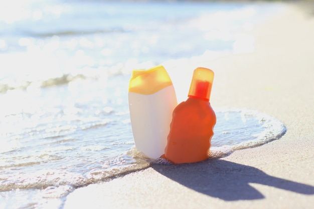 Acessórios de praia e protetores solares na areia à beira-mar. foto de alta qualidade