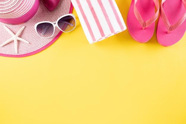 Acessórios de praia em fundo pastel amarelo para o conceito de férias de verão.