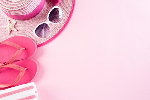 Acessórios de praia em fundo rosa pastel para o conceito de férias de verão.