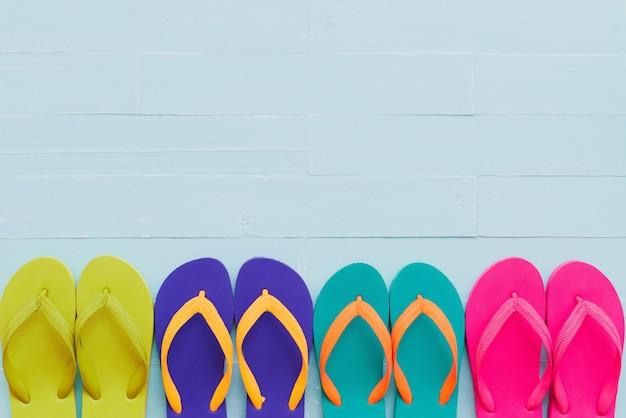 Acessórios de praia, incluindo o colorido flip flop no fundo de madeira pastel azul brilhante