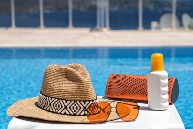 Acessórios de praia laranja perto da piscina. protetor solar, óculos escuros, alto-falante musical e chapéu de palha.