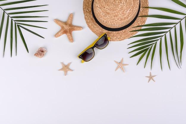 Acessórios de praia: óculos e chapéu com conchas e estrelas do mar em fundo branco. fundo de verão