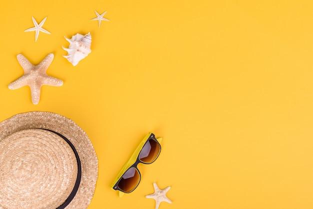 Acessórios de praia: óculos e chapéu com conchas e estrelas do mar sobre fundo colorido. fundo de verão Foto Premium