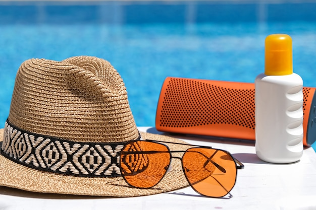 Acessórios de praia piscina. protetor solar, óculos escuros, alto-falante musical e chapéu de palha