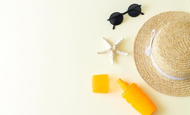 Acessórios de praia plana lay e vista superior do fundo do verão. chapéu de sol, óculos de sol, garrafa de protetor solar e estrela do mar com espaço de cópia