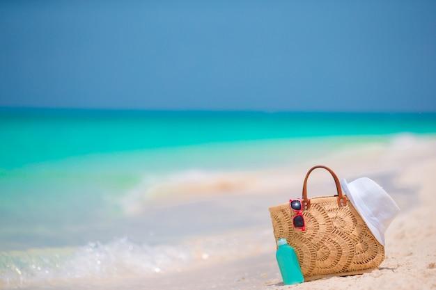 Acessórios de praia - saco de palha, chapéu branco e óculos de sol vermelhos na praia