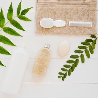 Acessórios de saúde da pele na mesa com folhas verdes