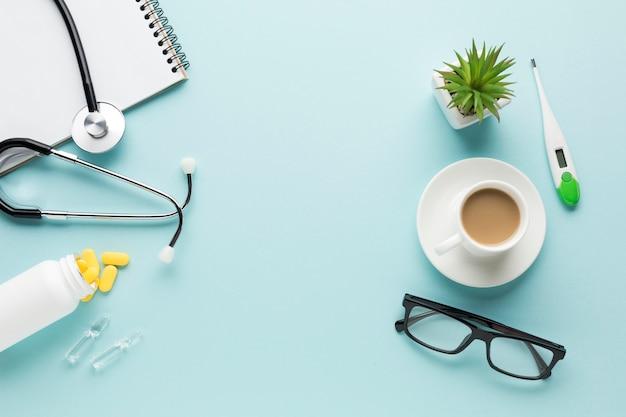 Acessórios de saúde; xícara de café e óculos sobre o pano de fundo azul