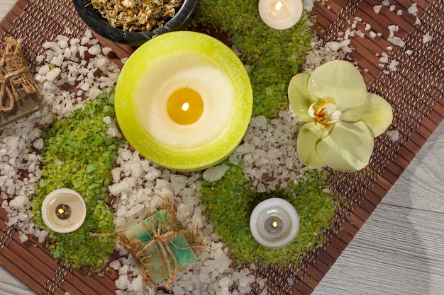 Acessórios de spa com sabonete, flor de orquídea amarela, tigela com flores de camomila secas, garrafas com óleo aromático, sal marinho, velas em guardanapo de bambu