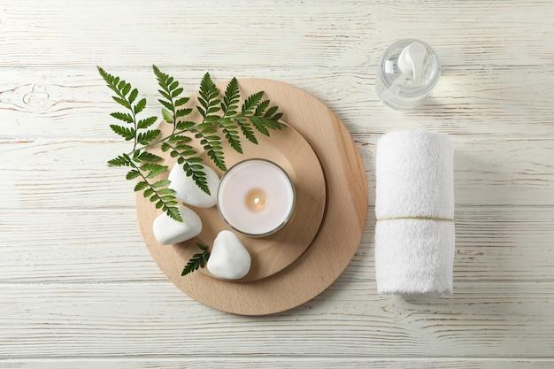 Acessórios de spa e ramo de samambaia em madeira branca, espaço para texto