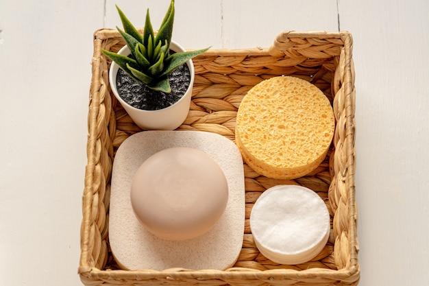 Acessórios de spa em casa - caixa de jacinto de água com esponjas, barras de sabão em fundo de madeira.