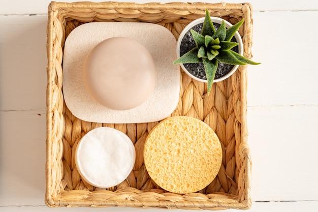 Acessórios de spa em casa caixa de jacinto de água com esponjas, barras de sabão em fundo de madeira.