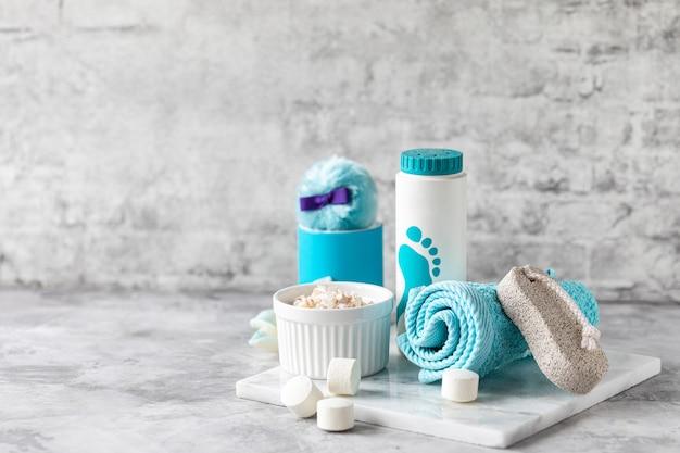 Acessórios de spa - sal marinho, pó, comprimidos para um banho, pedra-pomes, creme sobre um fundo claro. conceito de estilo de vida saudável. cosméticos para pés de cuidados com a pele. decoração para o banheiro.