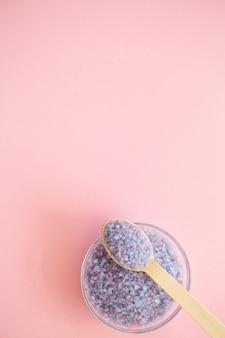 Acessórios de spa. tratamento de beleza de sal de banho em fundo rosa