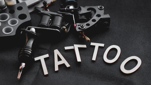 Acessórios de tatuagem com a tatuagem de inscrição de letras de madeira em uma superfície preta.