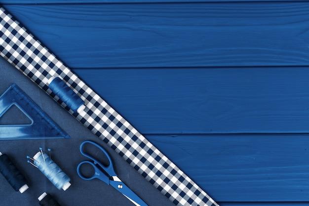 Acessórios de tayloring em fundo azul clássico, vista superior