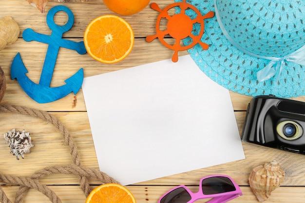 Acessórios de verão. acessórios de praia. chapéu, protetor solar, óculos escuros, câmera e laranja em uma mesa de madeira natural. vista do topo.