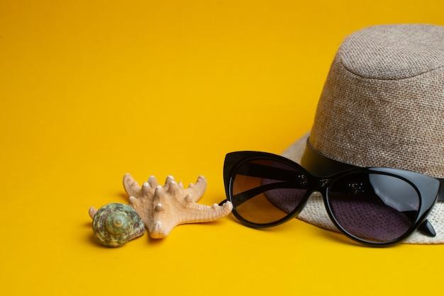 Acessórios de verão, conchas, chapéu e óculos de sol na superfície amarela.
