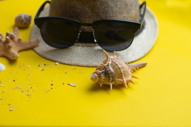 Acessórios de verão, conchas do mar, chapéu e óculos de sol. férias de verão e conceito de mar.