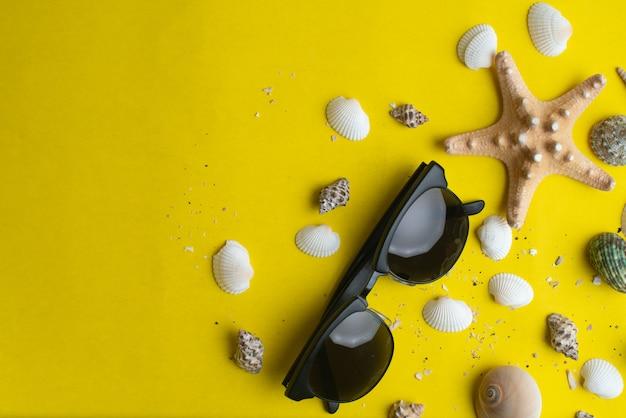 Acessórios de verão, conchas e óculos de sol na superfície amarela.
