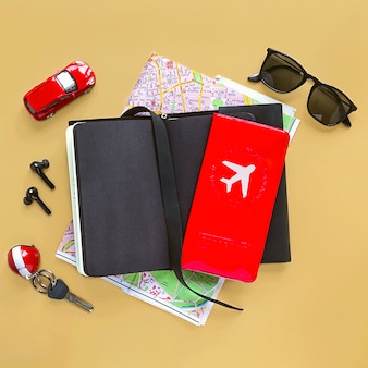 Acessórios de viagem masculina, caderno, mapa, airpods, óculos de sol, modelo do carro em fundo bege. vista superior, configuração plana.