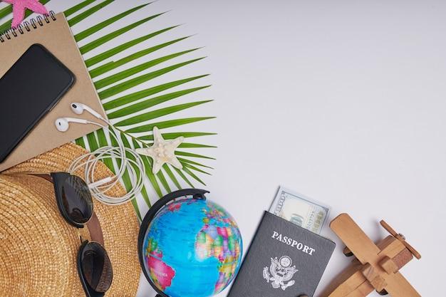 Acessórios de viagem plana leigos em fundo branco com folha de palmeira, câmera, chapéu, passaportes, dinheiro, globo, livro, telefone, mapa e óculos de sol. vista superior, conceito de viagens ou férias. fundo de verão.