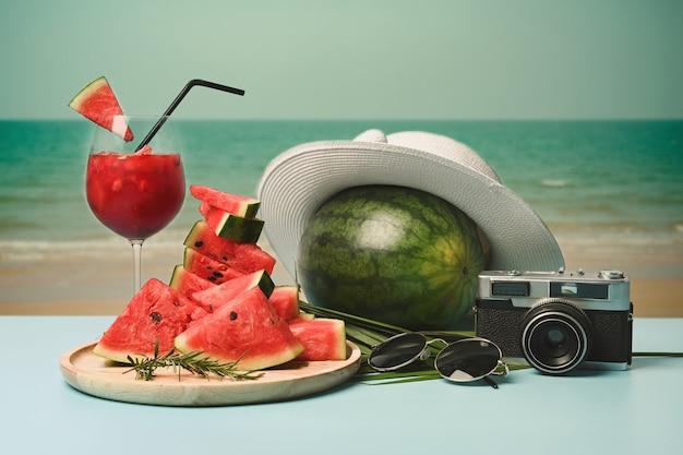 Acessórios de viajante e suco de melancia na mesa com fundo de praia de verão.