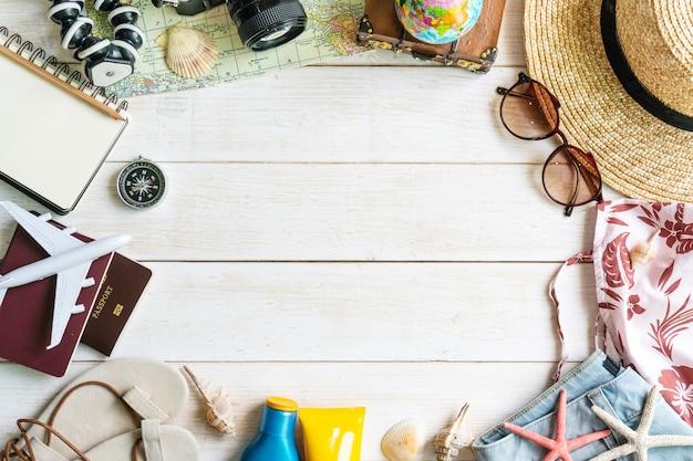 Acessórios de viajante plana leigos na mesa de madeira branca. vista superior conceito de viagens ou férias.