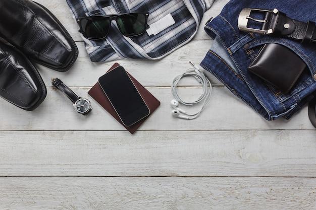 Acessórios de vista superior para viajar com o conceito de vestuário do homem. camisa, jean, telefone móvel em fundo de madeira. vestuário, óculos de sol e sapatos na mesa de madeira.