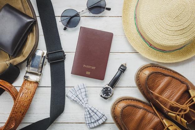 Acessórios de vista superior para viajar com o conceito de vestuário do homem. gravata de laço, carteira em fundo de madeira. relógio, óculos de sol, saco, chapéu e sapatos na mesa de madeira.