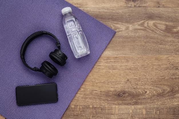 Acessórios desportivos no tapete de ioga. fones de ouvido, smartphone e uma garrafa d'água no chão. aptidão, conceito de estilo de vida saudável. vista do topo