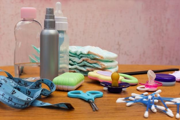 Acessórios do bebê: chupeta, garrafa, fraldas descartáveis, tesoura