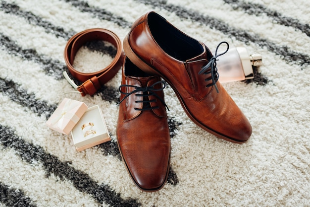 Acessórios do dia do casamento do noivo. sapatos de couro marrom, cinto, perfume, anéis de ouro. moda masculina