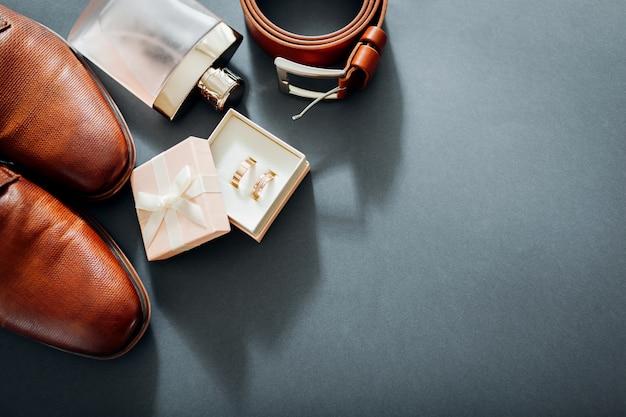 Acessórios do dia do casamento do noivo. sapatos de couro marrom, cinto, perfume, anéis de ouro.